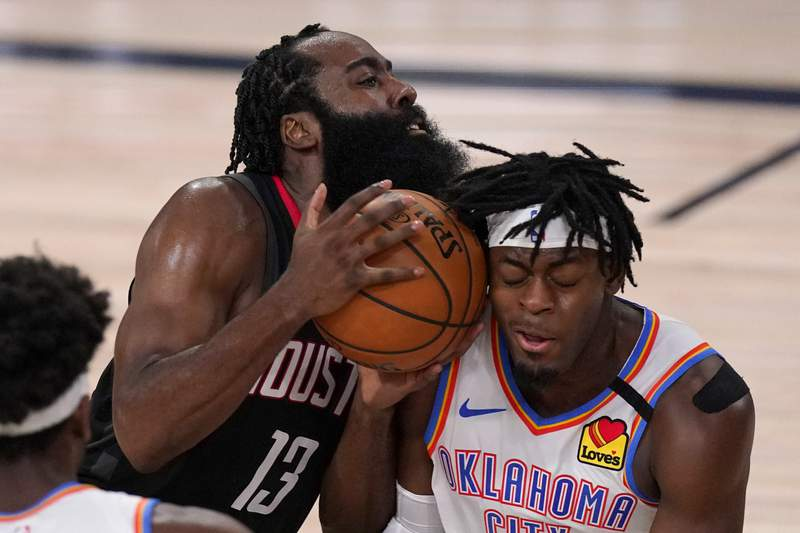Houston Rockets' James Harden (13) drives into Oklahoma City Thunder's Luguentz Dort (5), right, trying to get up court during the second half of an NBA first-round playoff basketball game in Lake Buena Vista, Fla., Wednesday, Sept. 2, 2020. (AP Photo/Mark J. Terrill)