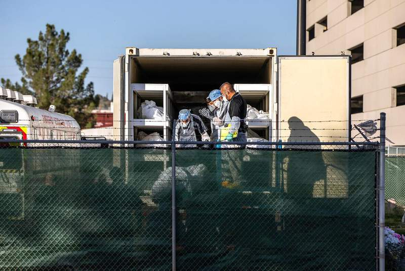 """El Paso County detention inmates, also known as """"trustees"""" who are low-level offenders, help move bodies to mobile morgue units outside the Medical Examiner's Office in El Paso on Nov. 14, 2020. (Credit: Ivan Pierre Aguirre for The Texas Tribune)"""