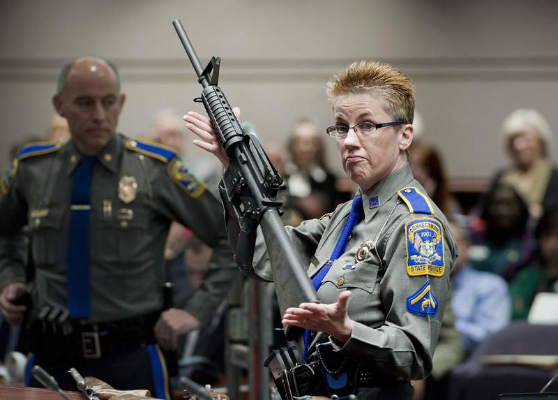 FILE - In this Jan. 28, 2013, record  photo, firearms grooming  portion   Detective Barbara J. Mattson, of the Connecticut State Police, holds up   a Bushmaster AR-15 rifle, the aforesaid  marque   and exemplary  of weapon  utilized  by Adam Lanza successful  the Sandy Hook School shooting, for a objection  during a proceeding  of a legislative subcommittee reviewing weapon  laws, astatine  the Legislative Office Building successful  Hartford, Conn. Remington, the shaper  of the firearm  utilized  successful  the Sandy Hook Elementary School shooting has offered immoderate   of the victims' families astir   $33 cardinal  to settee  their suit  implicit    however  the institution  marketed the firearm to the public. (AP Photo/Jessica Hill, File)