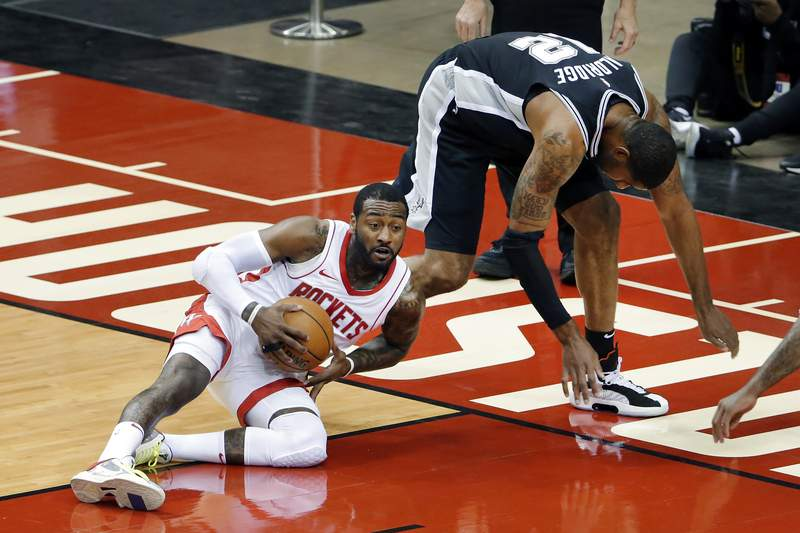 Houston Rockets guard John Wall (1) comes up with a loose ball in front of San Antonio Spurs forward LaMarcus Aldridge (12) during the first half of an NBA basketball game Tuesday, Dec. 15, 2020, in Houston. (AP Photo/Michael Wyke)