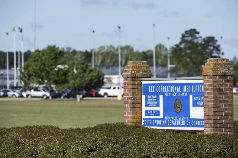 FILE - This Monday, April 16, 2018, file photo, shows a sign outside the Lee Correctional Institution in Bishopville, S.C. South Carolina's attorney general says 29 inmates have been charged in connection with a riot at the facility in 2018 that left seven inmates dead and 22 injured. (AP Photo/Sean Rayford, File)