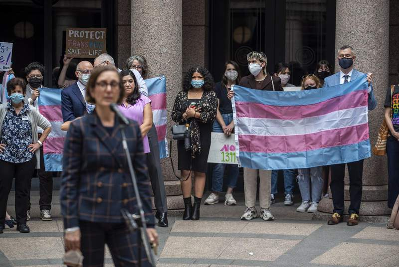 People hold up a transgender flag at an event held by Equality Texas at the Capitol on April 14. (Credit: Sergio Flores for The Texas Tribune)