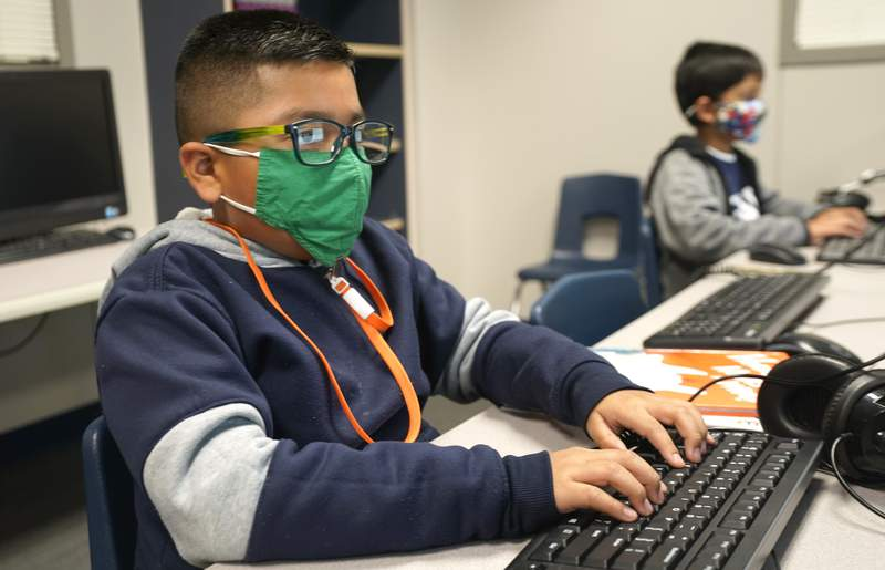 Masked students work on computers at Tibbals Elementary School in Murphy, Texas, Thursday, Dec. 3, 2020. Texas Gov. Greg Abbot's statewide mask order does not mandate face covering for children under the age of 10, allowing some school districts to not require masks for children leaving the choice of mask use up to the parents. (AP Photo/LM Otero)