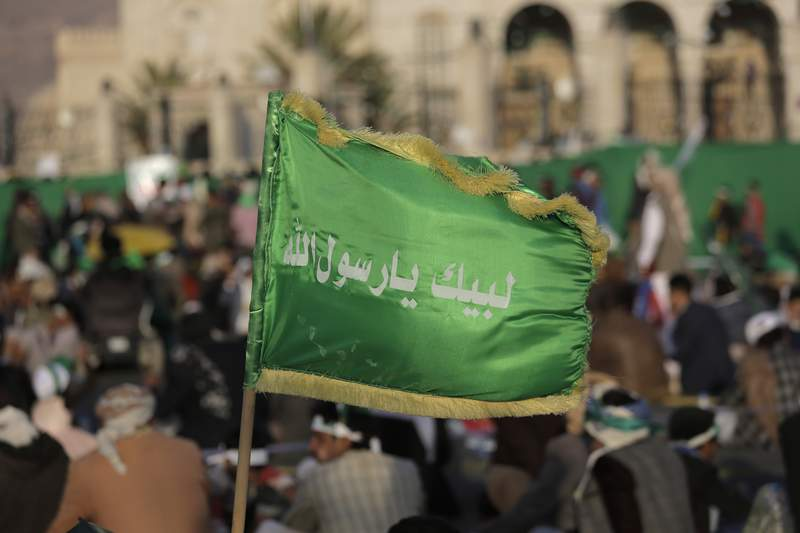 """FILE - In this Nov. 9, 2019 file photo, a supporter of Shiite rebels, known as Houthis, holds a banner with Arabic writing that reads, """"at your order, oh messenger of Allah,"""" during a celebration of Mawlid al-Nabi the birth of Islam's prophet Muhammad in Sanaa, Yemen. A drastic escalation in fighting between the Saudi-led military coalition and Houthi rebels in Yemen has killed and wounded hundreds of people over the past week, officials and tribal leaders said on Monday, Jan. 27, 2020.   (AP Photo/Hani Mohammed, File)"""