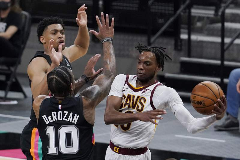 Cleveland Cavaliers guard Darius Garland, right, drives to the basket against San Antonio Spurs forward DeMar DeRozan (10) during the second half of an NBA basketball game in San Antonio, Monday, April 5, 2021. (AP Photo/Eric Gay)
