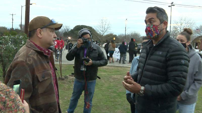 District 1 Councilman Roberto Treviño, right, speaks to a resident about the encampment outside his field office.