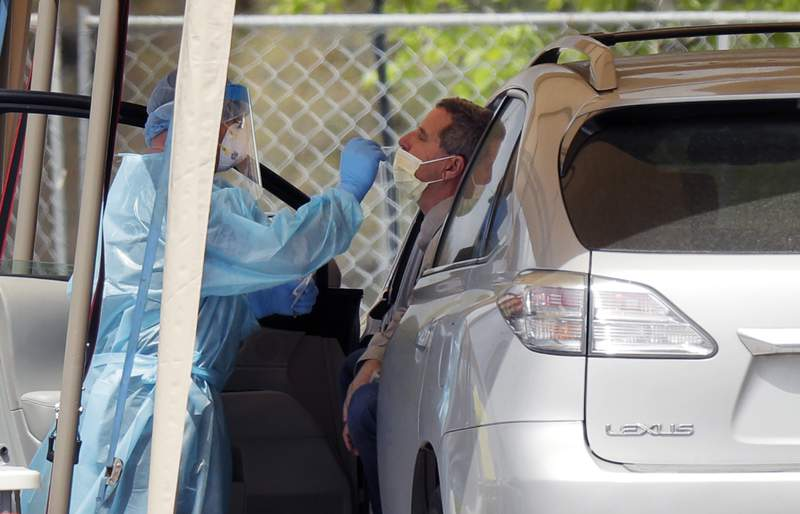 FILE - In this March 17, 2020, a medical worker tests a person for the coronavirus at a drive-thru facility in San Antonio. Nobody can say with precise certainty how many coronavirus tests that the NBA, NHL and Major League Baseball would need before those leagues can resume playing games. (AP Photo/Eric Gay, File)