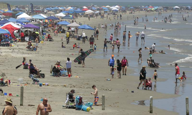 FILE- In this May 23, 2020, file photo people gather on the beach for the Memorial Day weekend in Port Aransas, Texas, Saturday, May 23, 2020.