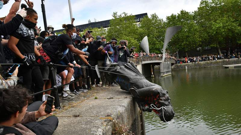 Black Lives Matter protests. Protesters throw statue of Edward Colston into Bristol harbour during a Black Lives Matter protest rally, in memory of George Floyd who was killed on May 25 while in police custody in the US city of Minneapolis. Picture date: Sunday June 7, 2020. See PA story POLICE Floyd. Photo credit should read: Ben Birchall/PA Wire URN:54052046 (Press Association via AP Images)