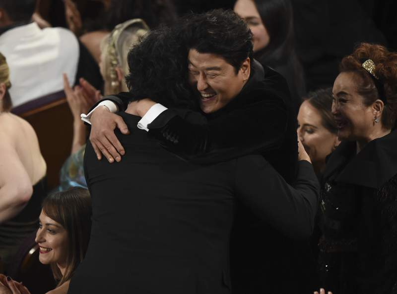 """Bong Joon Ho, left, is congratulated by Kang-Ho Song before going on stage to accept the award for best international feature film for """"Parasite,"""" from South Korea, at the Oscars on Sunday, Feb. 9, 2020, at the Dolby Theatre in Los Angeles. (AP Photo/Chris Pizzello)"""