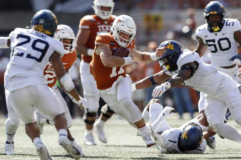 AUSTIN, TEXAS - NOVEMBER 07: Sam Ehlinger #11 of the Texas Longhorns rushes the ball defended by Josh Chandler-Semedo #7 of the West Virginia Mountaineers in the second quarter at Darrell K Royal-Texas Memorial Stadium on November 07, 2020 in Austin, Texas. (Photo by Tim Warner/Getty Images)