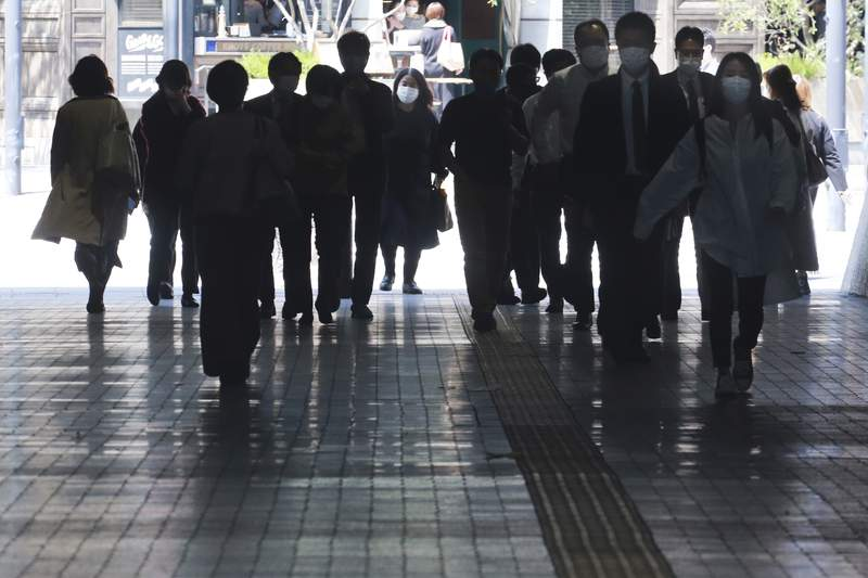 People wearing face masks to protect against the spread of the coronavirus walk on an underpass in Tokyo, Monday, April 12, 2021.  Japan started its vaccination drive with medical workers and expanded Monday to older residents, with the first shots being given in about 120 selected places around the country. (AP Photo/Koji Sasahara)