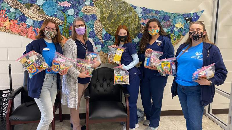 The Forever Vets Animal Hospital at Murabella team holds up the treat bags they are delivering to PVPV/Rawlings Elementary School.
