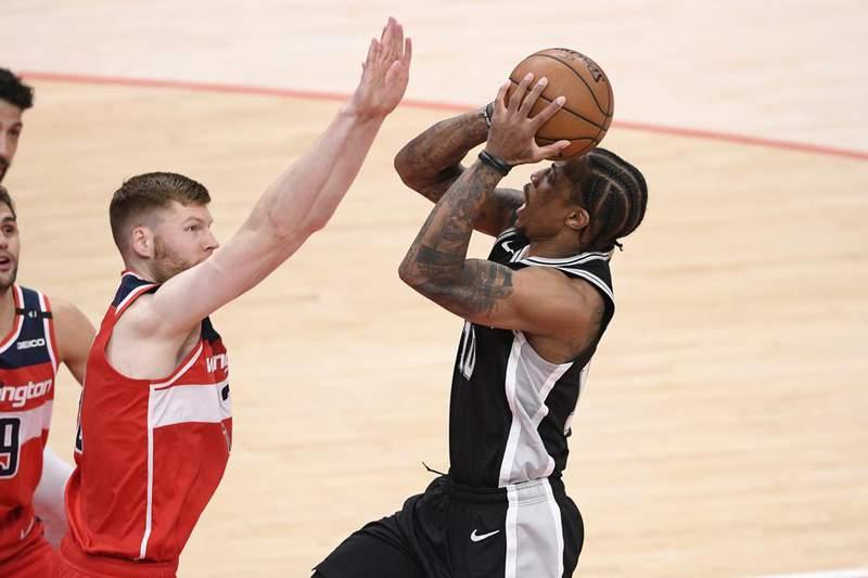 San Antonio Spurs forward DeMar DeRozan, right, goes to the basket against Washington Wizards forward Davis Bertans, left, during the first half of an NBA basketball game, Monday, April 26, 2021, in Washington.