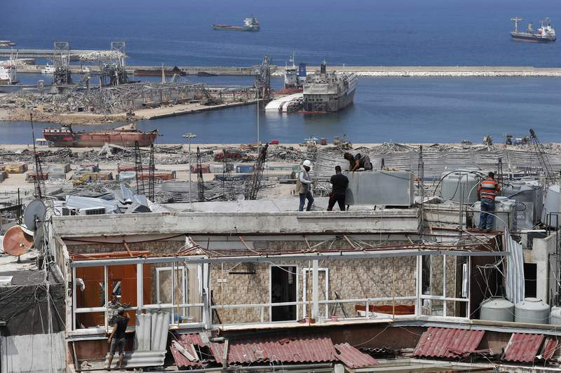 Workers repair water tanks and damaged apartments overlooking the site of the Aug. 4 explosion that hit the seaport, in Beirut, Lebanon, Thursday, Aug. 27, 2020. (AP Photo/Hussein Malla)