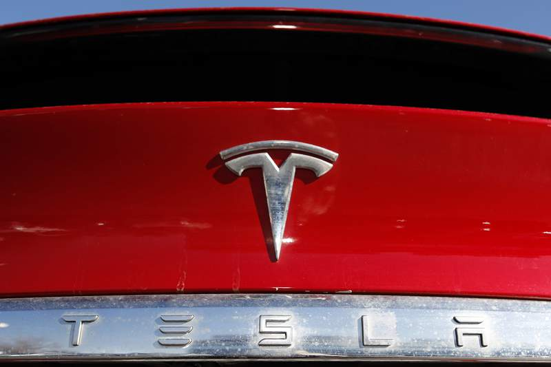 FILE - In this Feb. 2, 2020, file photo, the company logo appears on an unsold 2020 Model X at a Tesla dealership in Littleton, Colo.  A day after its 5-for-1 stock split took effect, Tesla is announcing plans to sell up to $5 billion worth of common shares.  Tesla shares rose over 2% in premarket trading Tuesday, Sept. 1,  after the filing with the U.S. Securities and Exchange Commission. (AP Photo/David Zalubowski, File)