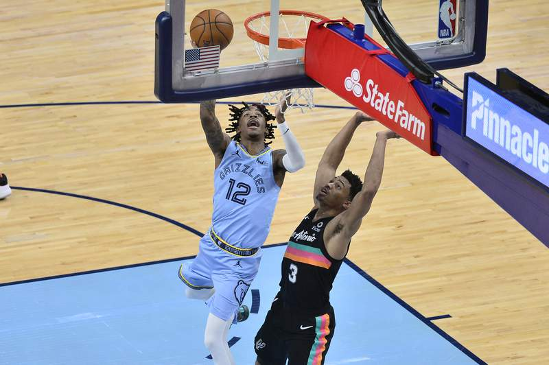 Memphis Grizzlies guard Ja Morant (12) shoots against San Antonio Spurs guard Keldon Johnson (3) in the second half of an NBA basketball game, Wednesday, Dec. 23, 2020, in Memphis, Tenn. (AP Photo/Brandon Dill)