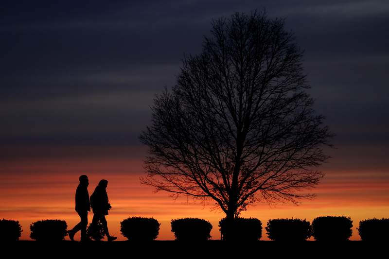 FILE - In this Monday, April 13, 2020 file photo, a couple walks alone in a Kansas City, Mo., park at sunset as stay-at-home orders continue in much of the country in an effort to stem the spread of the new coronavirus. When most of the U.S. went into lockdown in 2020, some speculated that confining couples to their homes with little to entertain themselves would lead to a lot of baby-making. But the statistics suggest the opposite happened. (AP Photo/Charlie Riedel)