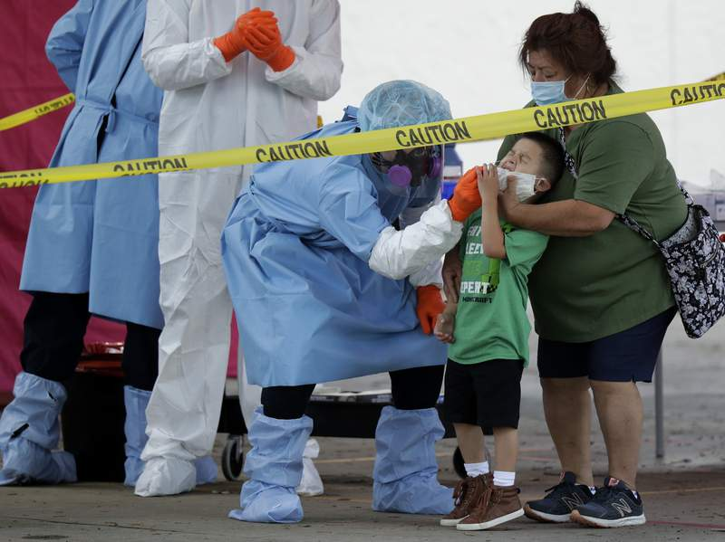 Jerry A Mann, second from right, is held by his grandmother, Sylvia Rubio, as he is tested for COVID-19 by the San Antonio Fire Department at a free walk-up test site set up to help underserved and minority communities in San Antonio, Thursday, May 14, 2020. Texas attorney general Ken Paxton has warned officials in San Antonio, Austin and Dallas that the cities could face lawsuits if they do not relax coronavirus measures he says go further than state law allows. (AP Photo/Eric Gay)