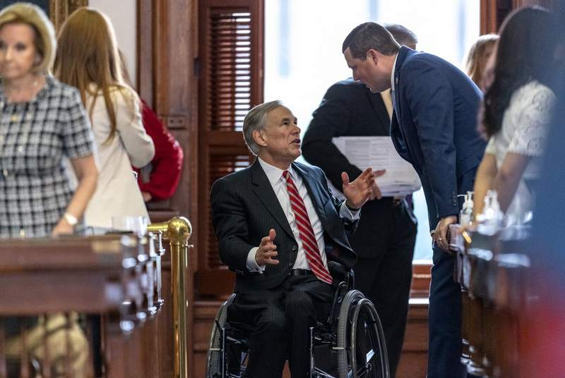 Gov. Greg Abbott speaks with lawmakers on the House floor during the legislative session on May 23, 2021.