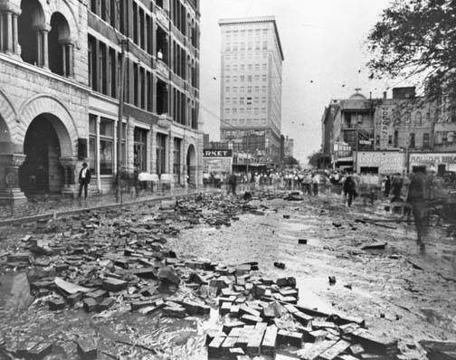 Photograph shows view looking north, from river bridge, toward intersection with College Street.  Texas State Bank and Trust Company on ground floor of the Grayburg Building on left.