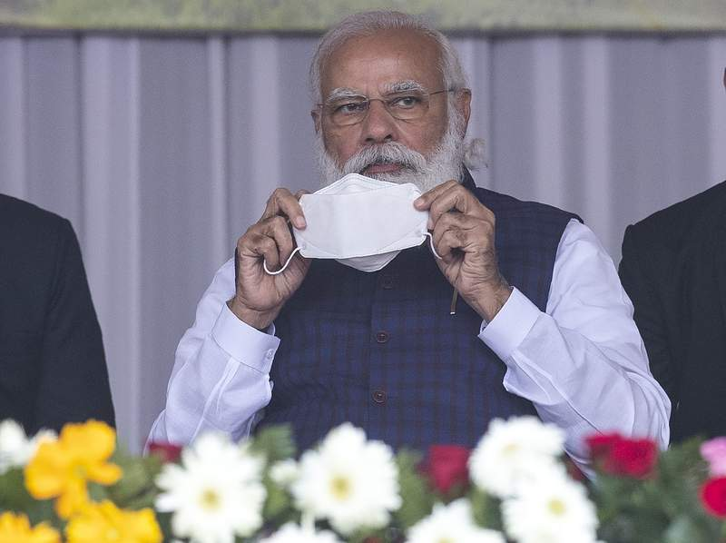 Indian Prime Minister Narendra Modi holds a face mask as he attends a a rally in Sivsagar, east of Gauhati, India, Saturday, Jan. 23, 2021. Modi attended a rally to distribute land allotment certificates to landless indigenous people in Assams Sivasagar district, under a special programme of the state government. (AP Photo/Anupam Nath)