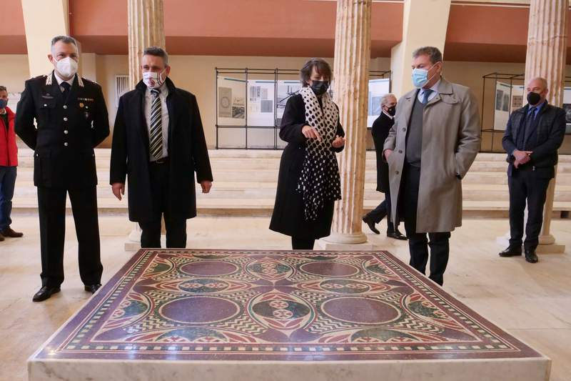 Authorities stand around a 1.5 square meter colorful mosaic dating back to 40 A.D. and belonging to the flooring of Caligulas lavish ceremonial ships, that was found thanks to a joint police operation in the rooms of a Manhattan house and returned to the museum of Nemi, near Rome, Thursday, March 11, 2021. In September 2017, the department for cultural heritage protection of the Italian Carabinieri police, in collaboration with New York district attorney, managed to sequester the mosaic from the house of an Italian-American woman who brought it in the states illegally many decades earlier. (AP Photo/Paolo Santalucia)