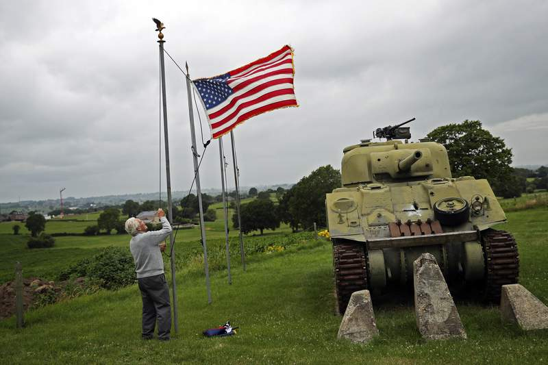 FILE - In this Wednesday, July 1, 2020 file photo, Marcel Schmetz raises the US flag next to a WWII American Sherman tank at his Remember Museum 39-45 in Thimister-Clermont, Belgium. Tourists from the United States who are fully vaccinated against COVID-19 could be able to travel across the European Union this summer, officials from the 27-nation bloc said on Monday, April 26, 2021. (AP Photo/Francisco Seco, File)