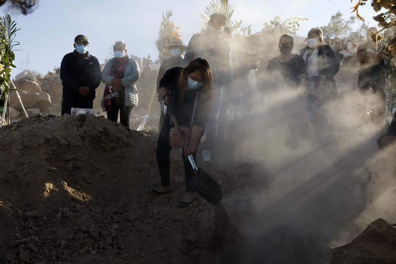 A family member shovels dirt into the grave of Giro Quispe who died from complications related to the new coronavirus, at El Cebollar cemetery, in Arequipa, Peru, Friday, June 25, 2021. Due to increased cases of COVID-19 and the Delta variant of the disease, the city is under a strict lockdown for 15 days beginning June 21. (AP Photo/Guadalupe Pardo)