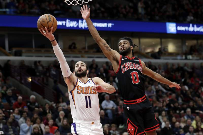 FILE - Phoenix Suns guard Ricky Rubio, left, drives to the basket past Chicago Bulls guard Coby White during the second half of an NBA basketball game in Chicago, in this Feb. 22, 2020, file photo. A person with knowledge of the situation says All-Star guard Chris Paul is being traded from the Oklahoma City Thunder to the Phoenix Suns, where he'll play alongside one of the league's most dynamic young scorers in fellow All-Star Devin Booker. The Thunder are acquiring Ricky Rubio, Kelly Oubre, Jalen Lecque, Ty Jerome and a first-round pick that will be conveyed sometime between 2022 and 2025, said the person who spoke to The Associated Press on condition of anonymity because the trade had not been finalized by the league. (AP Photo/Nam Y. Huh, File)
