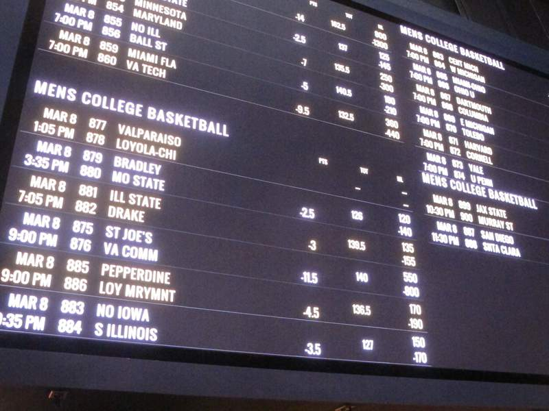 A betting board lists the odds on college basketball games in the sports betting facility at the Tropicana casino in Atlantic City, N.J. on March 8, 2019, the last year the March Madness tournament was held. The American Gaming Association predicts 47 million people will bet on this year's tournament, about the same as two years ago. But 8% fewer plan to fill out brackets pools because many offices remain closed due to the coronavirus pandemic. (AP Photo/Wayne Parry)