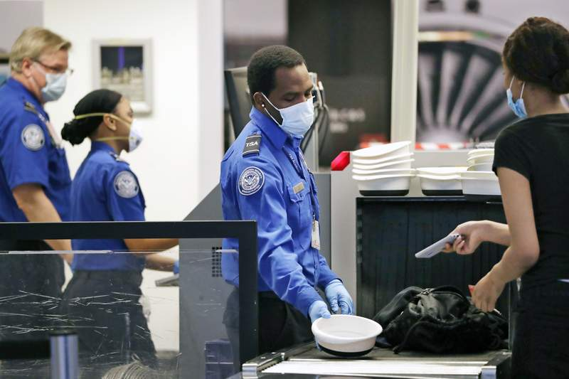 TSA officers wear protective masks at a security screening area at Seattle-Tacoma International Airport Monday, May 18, 2020, in SeaTac, Wash. Airlines say they are stepping up security on flights to Washington before next weeks inauguration of President-elect Joe Biden. Delta, United and Alaska airlines said Thursday, Jan. 14, 2021 they will bar passengers flying to Washington from putting guns in checked bags. (AP Photo/Elaine Thompson)