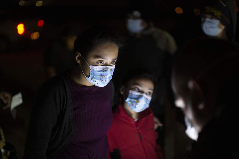 Fatima Nayeli, 13, left, ands her sister, Cynthia Stacy, 8, answer questions from a U.S.Border Patrol agent at an intake site after they were smuggled on an inflatable raft across the Rio Grande river in Roma, Texas, Wednesday, March 24, 2021. The sisters traveled from El Salvador in the hope of reaching relatives living in the U.S. On Wednesday, President Joe Biden tapped Vice President Kamala Harris to lead the White House efforts at the U.S. southern border and work with Central American nations to address root causes of the migration. (AP Photo/Dario Lopez-Mills)