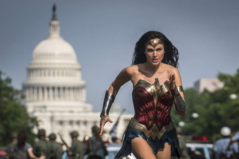 """This image released by Warner Bros. Pictures shows Gal Gadot as Wonder Woman in a scene from """"Wonder Woman 1984."""" The film isn't skipping theaters or moving to 2021, but it is altering course. The last big blockbuster holdout of 2020 is still opening in U.S. theaters on Christmas Day but it will also be made available to HBO Max subscribers free of charge for its first month, Warner Bros. said Wednesday, Nov. 18, 2020. (Clay Enos/Warner Bros Pictures via AP)"""