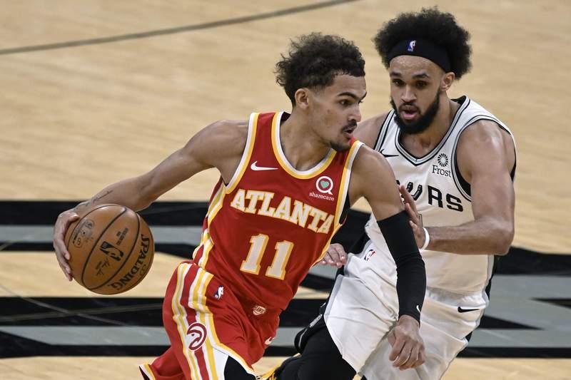 Atlanta Hawks' Trae Young (11) drives against San Antonio Spurs' Derrick White during the second half of an NBA basketball game Thursday, April 1, 2021, in San Antonio. (AP Photo/Darren Abate)