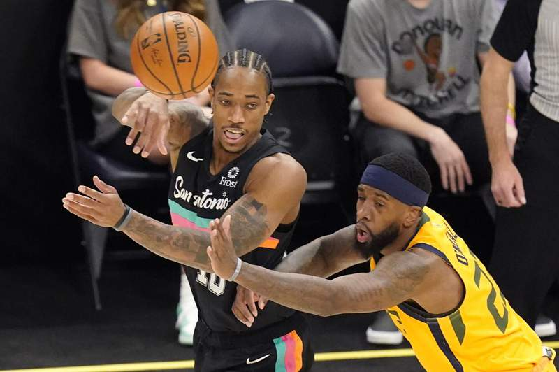 San Antonio Spurs forward DeMar DeRozan, left, passes the ball as Utah Jazz forward Royce O'Neale, right, defends in the first half during an NBA basketball game Monday, May 3, 2021, in Salt Lake City