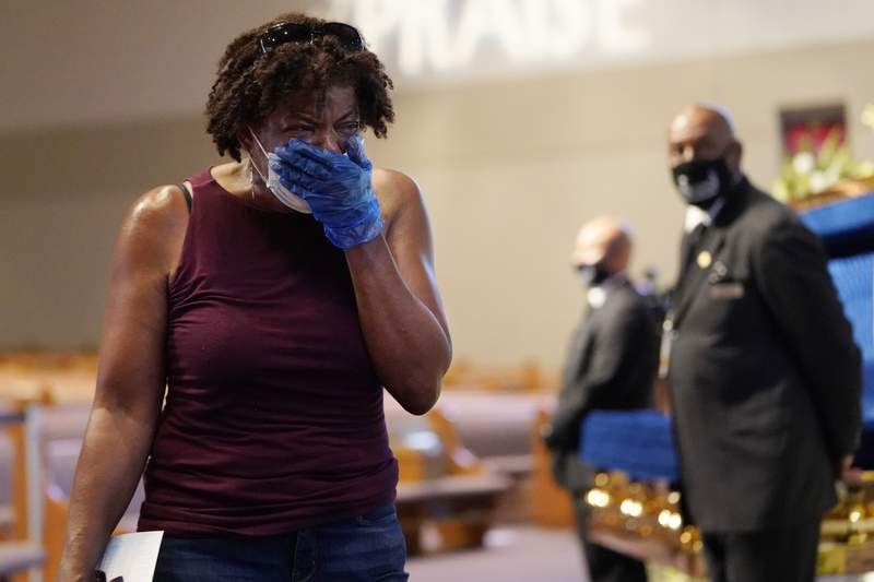 Mourner Charlene Thompson, of Houston, passes by the casket of George Floyd during a public visitation for Floyd at the Fountain of Praise church Monday, June 8, 2020, in Houston. (AP Photo/David J. Phillip, Pool)