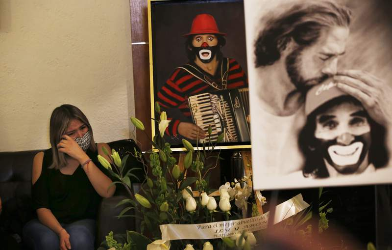 """A woman wipes tears during the wake of Ricardo González Gutiérrez, the legendary clown known as Cepillín, or """"Little Toothbrush,"""" at a funeral home in Tlalnepantla de Baz, the State of Mexico, Tuesday, March 9, 2021. Also a singer, TV host, and actor, the 75-year-old started his career as a dentist who painted his face so kids would not be afraid of him as he worked on their teeth. (AP Photo/Marco Ugarte)"""