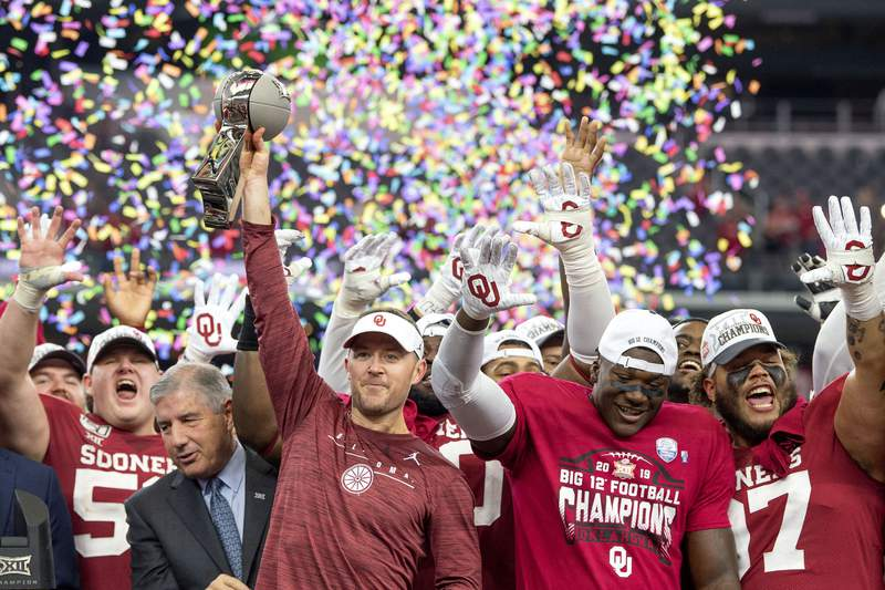 FILE - In this Dec. 7, 2019, file photo, Oklahoma head coach Lincoln Riley hosts the Big 12 Conference championship trophy after defeating Baylor 30-23 in overtime in an NCAA college football game in Arlington, Texas. Riley will earn an average of more than $7.5 million a year under a contract extension through the 2025 season. The university's board of regents approved the two-year extension Tuesday, July 28, 2020. (AP Photo/Jeffrey McWhorter, File)