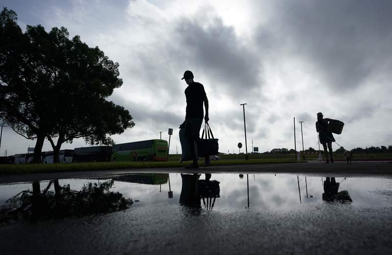 People looking to evacuate the path of Hurricane Laura arrive at the civic center where evacuation buses wait, Wednesday, Aug. 26, 2020, in Port Arthur, Texas. Hurricane Laura is expected to make landfall in the area Wednesday night or early Thursday. (AP Photo/Eric Gay)