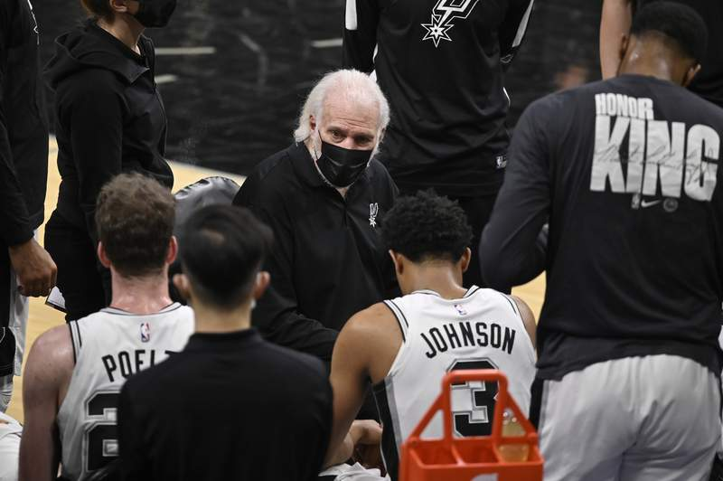 San Antonio Spurs head coach Gregg Popovich, center, talks to his players during a time out in the first half of an NBA basketball game against the Washington Wizards, Sunday, Jan. 24, 2021, in San Antonio. San Antonio won 121-101. (AP Photo/Darren Abate)