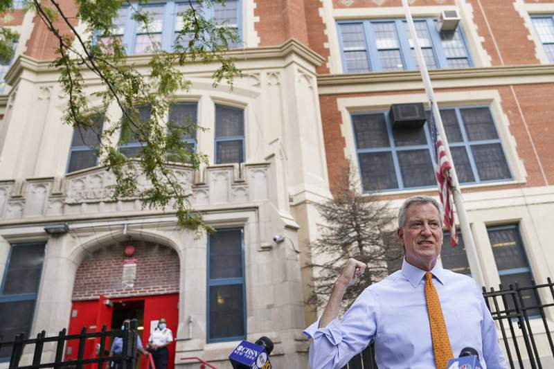FILE  In this Aug. 19, 2020 file photo, New York Mayor Bill de Blasio speaks to reporters after visiting New Bridges Elementary School to observe pandemic-related safety procedures, in the Brooklyn borough of New York. New York City is delaying the start of its school year by several days to give teachers more time to prepare to have students back in classrooms amid the coronavirus pandemic, Mayor Bill de Blasio announced Tuesday, Sept. 1.  (AP Photo/John Minchillo, FIle)