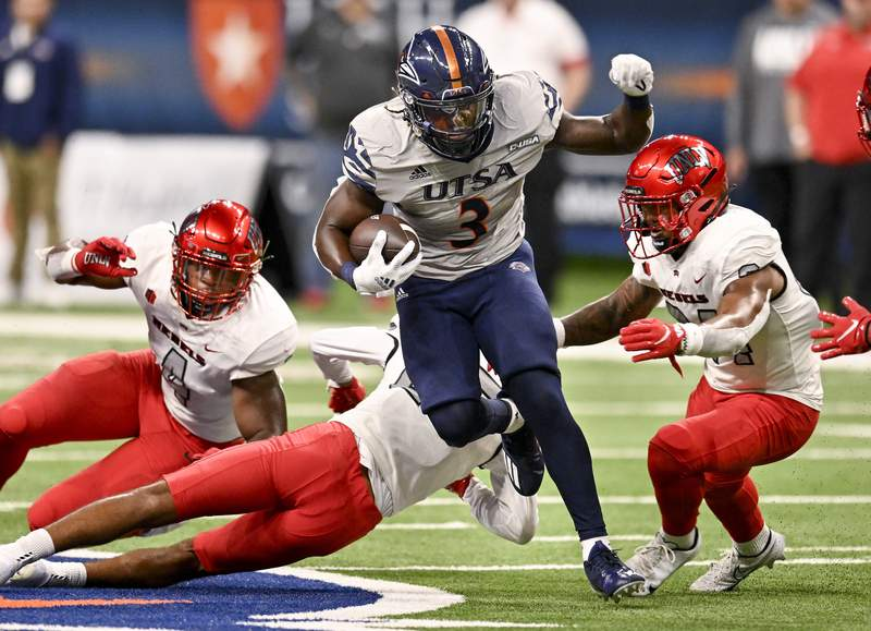 UTSA's Sincere McCormick (3) attempts to evade UNLV's Bryce Jackson, right, Jacoby Windmon, left, and Cameron Oliver during the first half of an NCAA football game on Saturday, Oct. 2, 2021, in San Antonio, Texas. (AP Photo/Darren Abate)