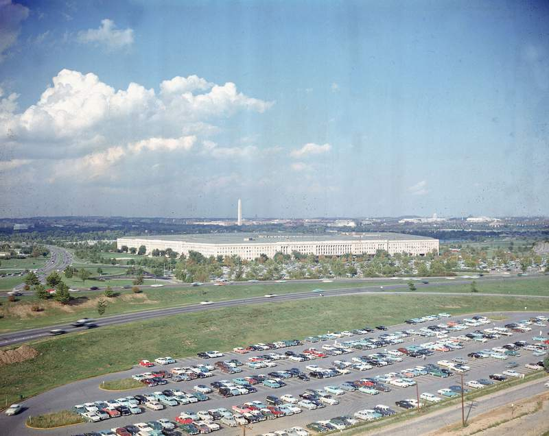 File-This undated file photo shows the Pentagon, headquarters of the U.S. Department of Defense, with the Washington Monument in background and a large parking lot in foreground, in Arlington, Va.  The Pentagon is proposing to end an arrangement in which a single military officer leads two of the nation's main cybersecurity organizations, a move that a leading Democrat said Saturday, Dec. 19, 2020, makes him profoundly concerned amid a large-scale cyberattack on U.S. government computer systems.  (AP Photo, File)