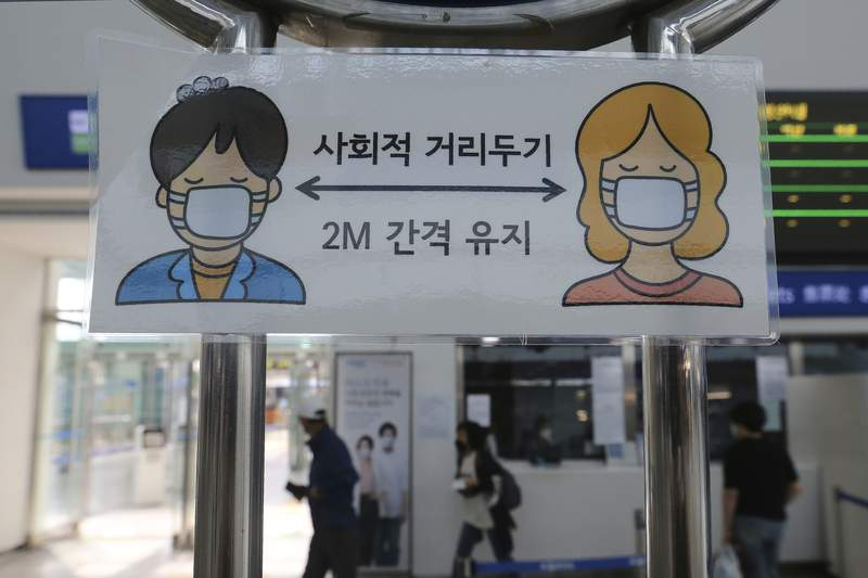 """A social distancing sign is seen at the Seoul Railway Station in Seoul, South Korea, Tuesday, Aug. 18, 2020. South Korea will ban large public gatherings and shut down churches and nightspots in the greater capital area following an alarming surge in coronavirus cases. The signs read """"Social distance and keep 2 meter away."""" (AP Photo/Ahn Young-joon)"""