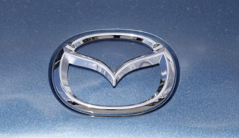 In this June 14, 2020, photograph, a Mazda company logo shines on the front of an unsold 2020 Miata at a Mazda dealership in Littleton, Colo. On Thursday, Nov. 19, Mazda beat traditional winners Lexus and Toyota to win top honors as the most dependable auto brand in Consumer Reports annual reliability survey.   Reports surveyed organization members who own more than 300,000 vehicles from model years 2000 to 2020.  (AP Photo/David Zalubowski)