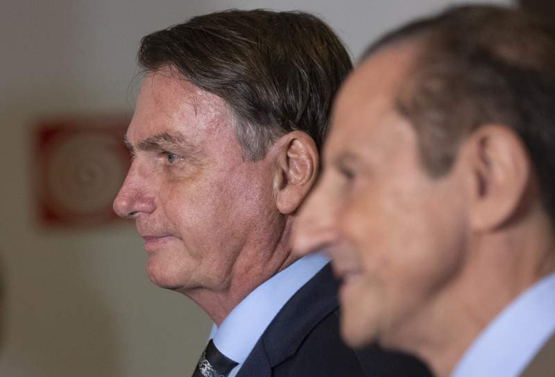 Brazilian President Jair Bolsonaro, left, and Paulo Skaf, president of the Sao Paulo's Industries Federation, FIESP, arrive for a meeting with Brazilian businessmen in Sao Paulo, Brazil, Monday, Feb. 3, 2020. (AP Photo/Andre Penner)