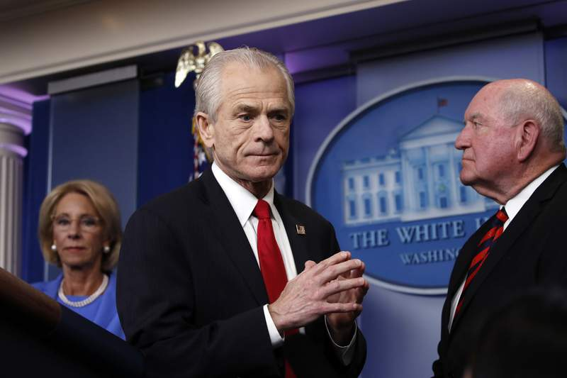 White House trade adviser Peter Navarro, who will now serve as national defense production act policy coordinator, walks from the podium after speak about the coronavirus in the James Brady Press Briefing Room, Friday, March 27, 2020, in Washington. Watching as Education Secretary Betsy DeVos and Agriculture Secretary Sonny Perdue watch. (AP Photo/Alex Brandon)