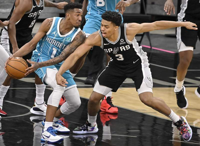 San Antonio Spurs' Keldon Johnson (3) attempts to steal the ball from Charlotte Hornets' Malik Monk during the first half of an NBA basketball game on Monday, March 22, 2021, in San Antonio. (AP Photo/Darren Abate)