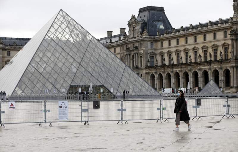 A woman wearing a protective face mask walks past the deserted Napoleon courtyard and the closed Louvre museum and pyramid in Paris, France.